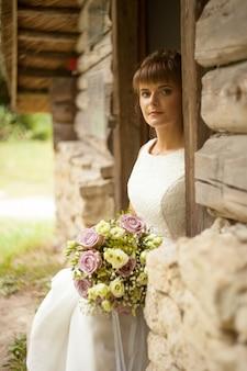 소박한 스타일의 아름다운 신부 초상화. 신부 헤어스타일. 장미 꽃다발입니다.