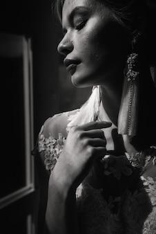 흰색 사진 스튜디오, 거울 및 소파에서 웨딩 드레스를 입고 포즈를 취하는 아름 다운 신부.