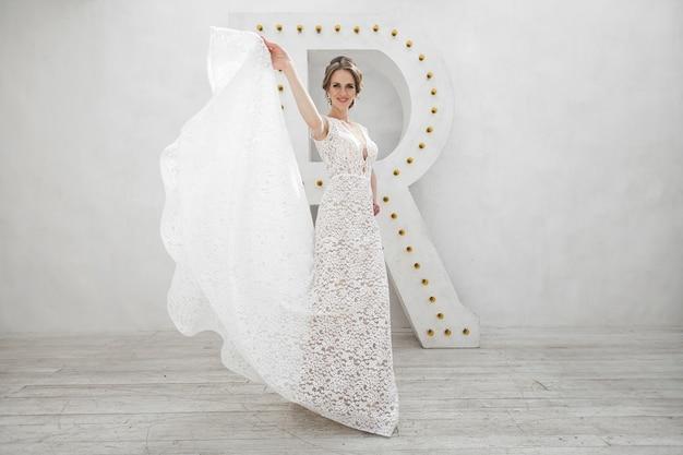 흰색 사진 스튜디오에서 웨딩 드레스를 입고 포즈를 취하는 아름 다운 신부. 거울. 소파. 꽃다발. 문. 샹들리에.