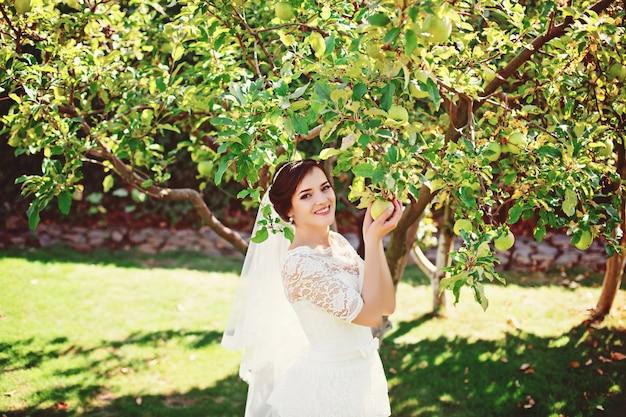Красивая невеста позирует возле дерева