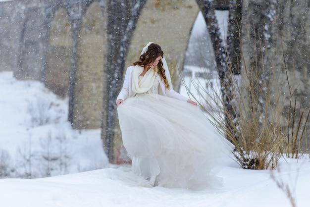Красивая невеста представляя около покинутого старого моста акведука. невеста восхищается ее платьем