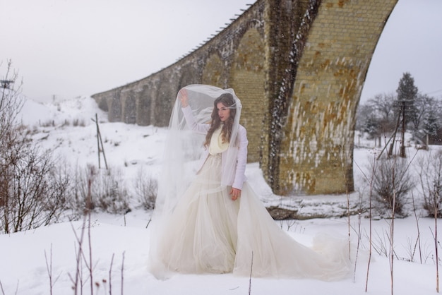 Красивая невеста представляя около покинутого старого моста акведука. невеста играет вуаль.