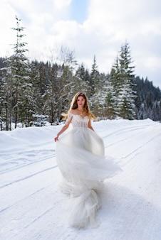 Красивая невеста позирует на фоне елового леса.