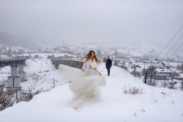 Красивая невеста позирует на старый заброшенный мост акведука. невеста крутится. жених смотрит на нее.