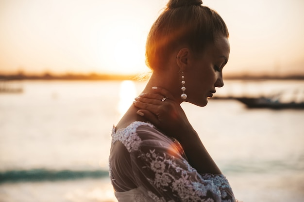 Красивая невеста позирует на пляже за морем на закате