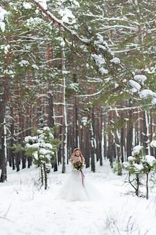 Красивая невеста позирует с букетом в снежном лесу. зимняя свадьба. произведение. полный портрет