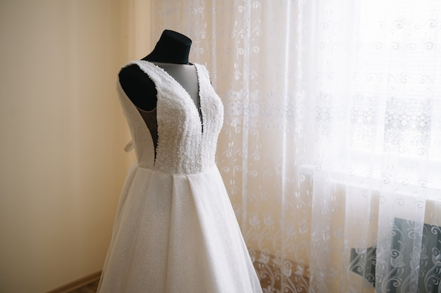 Beautiful bride's white wedding dress hangs near the bed in a hotel room with flowers at the bottom
