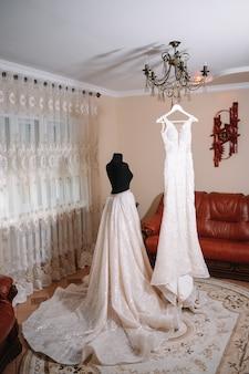 아름다운 신부의 하얀 웨딩 드레스가 호텔 방의 침대 근처에 꽃이 달린 바닥에 매달려 있습니다.