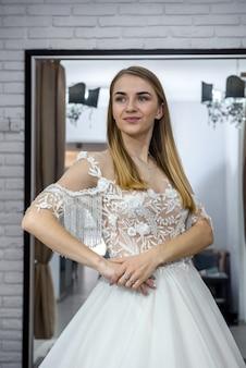 Beautiful bride in salon posing in wedding dress