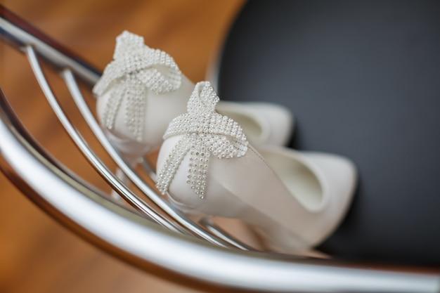 美しい花嫁の靴をクローズアップ。椅子の後ろにハイヒールのブライダルシューズ。エレガントな女性の白い靴のペアは、光沢のあるラインストーンと半貴石で弓を飾りました。ブライダルアクセサリー