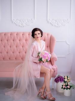 Красивая невеста сидит в розовом шелковом халате и вуалью на роскошном розовом диване