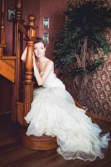 Красивая невеста сидит на деревянной лестнице
