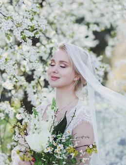 美しい花嫁は公園の花の木のにおいがします。花と結婚式のテーマ