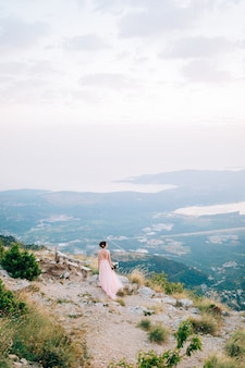 Beautiful bride and standing on the mountain, holding bouquet and looking at the bay of kotor.