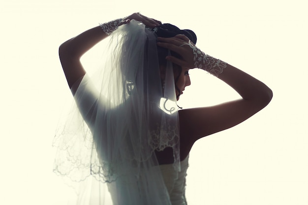 Beautiful bride standing near window. the girl in a white wedding dress.