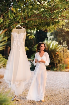 A beautiful bride stands next to a wedding dress with a cup of tea in a boudoir outfit next to a villa in italy.morning of the bride in tuscany.
