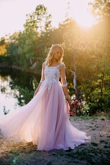 Beautiful bride stands with a bouquet in hands on a nature background