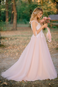 Beautiful bride stands with a bouquet in hands on a nature
