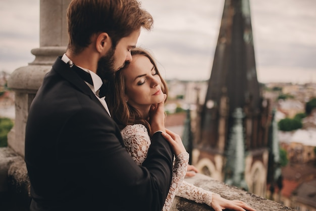 Beautiful bride and stylish groom are hugging on the balcony of old gothic cathedral with panoramic city views