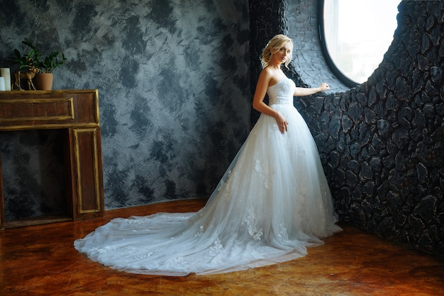 A beautiful bride in a very beautiful long dress with a train stands by the window.