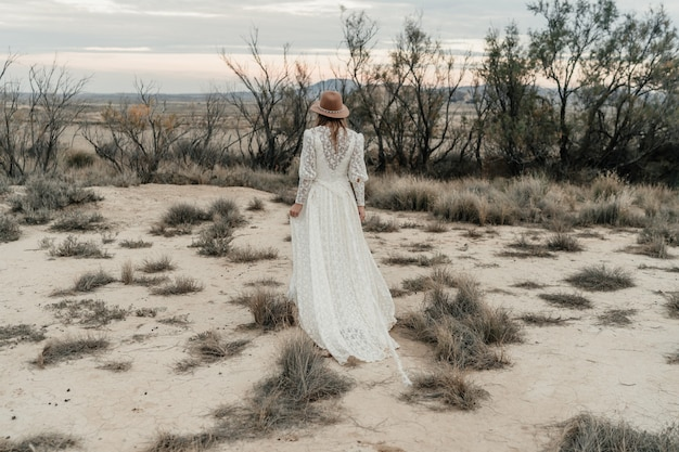 Bella sposa che cammina in una terra con cespugli e alberi secchi al tramonto
