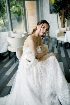 Красивая невеста в модном свадебном платье в красивом ресторане