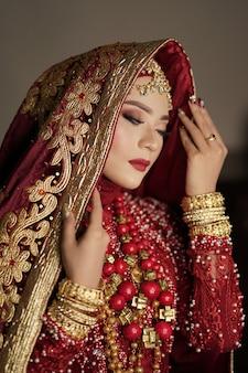 빨간색과 금색 드레스를 입고 아름다운 신부