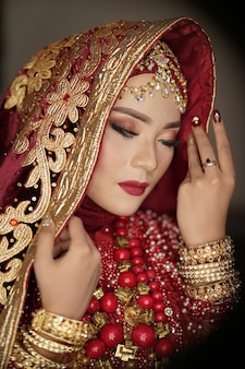 Beautiful bride wearing a red and gold dress