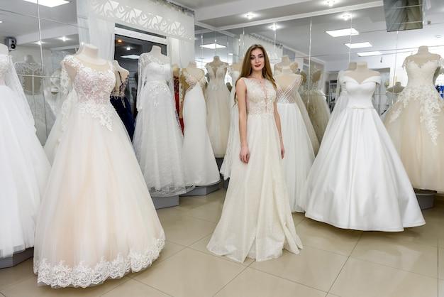 Beautiful bride wearing wedding dress in salon