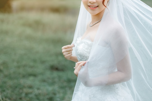 A beautiful bride wearing a wedding ring holds her veil.