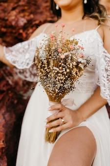 Bella sposa che indossa un abito bianco e che tiene un mazzo di fiori