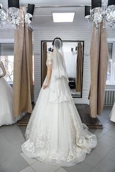 Beautiful bride in wedding dress posing before mirror