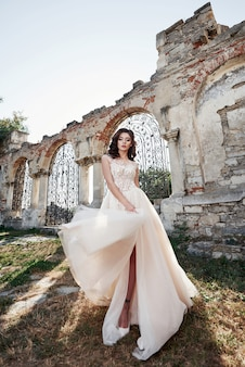 Beautiful bride in wedding dress, which is photographed on the wedding day near the old castle.