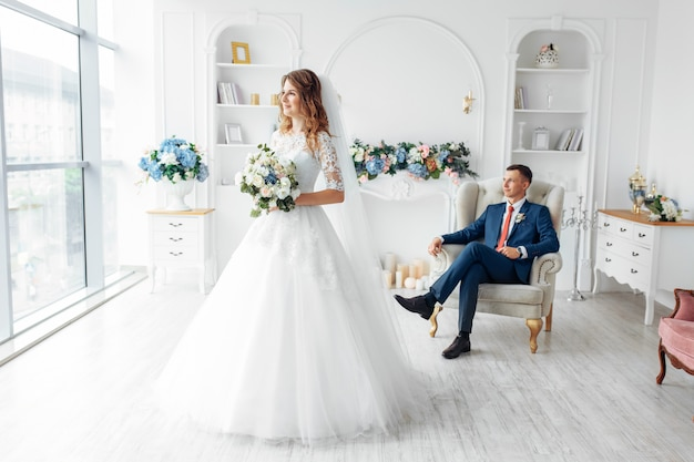 Beautiful bride in white dress and groom in suit, posing in white studio interior, wedding