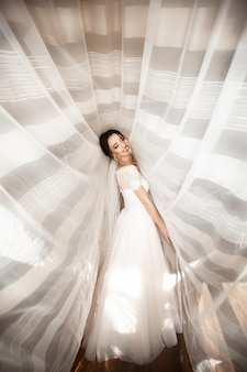 Beautiful bride in white dress posing under curtain