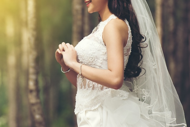 Beautiful bride white dress stand smile waiting  bridegroom outdoors in a forest