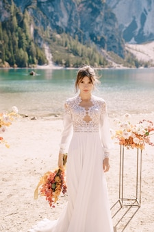 Beautiful bride in a white dress with sleeves and lace, with a yellow autumn bouquet, posing at lago di braies in italy