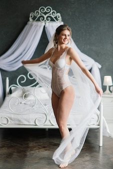 Beautiful bride in white lingerie lying on the bed in her bedroom