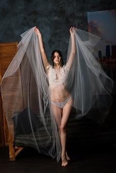 Beautiful bride in white lingerie sitting in her bedroom