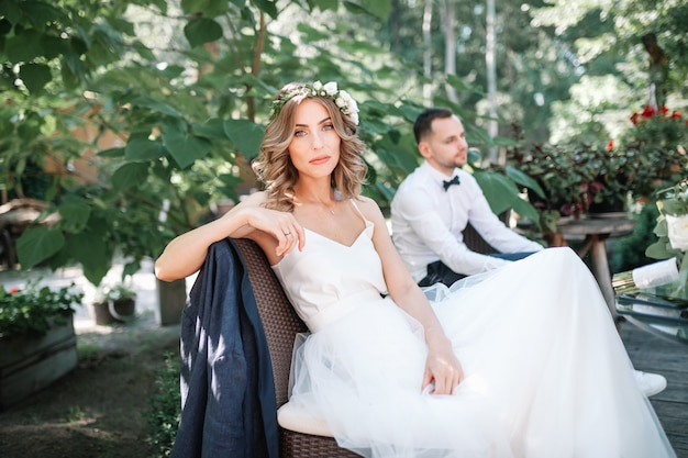 A beautiful bride in a white wedding dress and wreath sits on a chair next to the groom