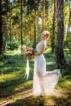 Красивая невеста с букетом в руке позирует в день своей свадьбы среди зеленых деревьев