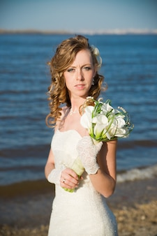 夏の川の海岸にオランダカイウの花束を持つ美しい花嫁プロのメイクと髪型