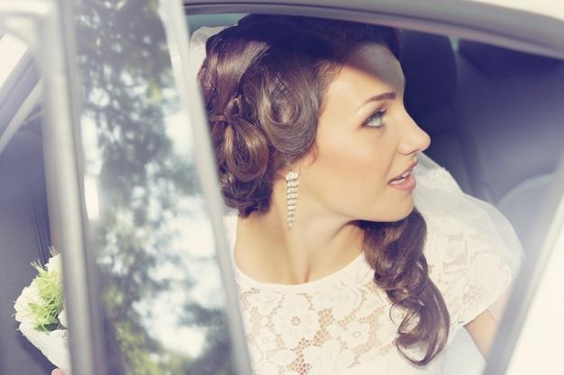 Красивая невеста с букетом роз, сидя в машине