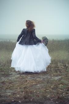 Красивая невеста с букетом на фоне туманного поля