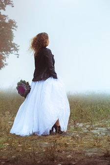 Красивая невеста с букетом на туманном поле