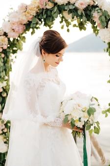 結婚式のアーチの近くにベールとブライダルブーケを持つ美しい花嫁