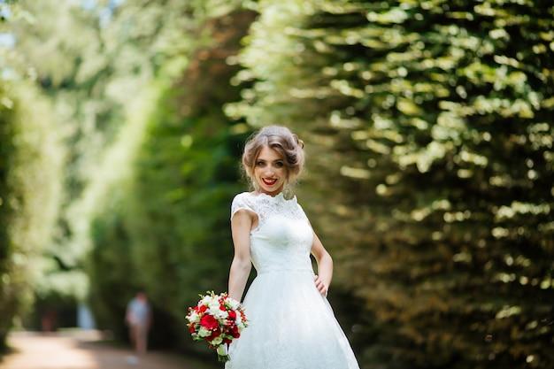 屋外の公園で彼女の手でウェディングブーケを持つ美しい花嫁