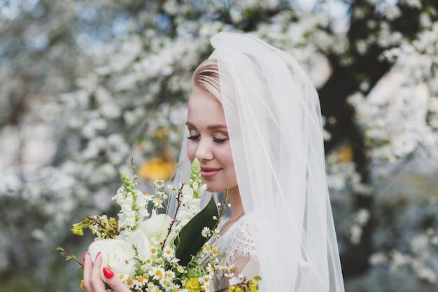 公園で屋外の花の花束を持つ美しい花嫁