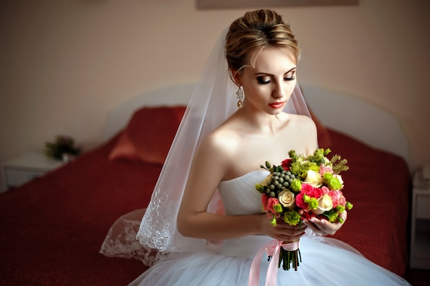 Beautiful bride with bouquet sitting on a bed.