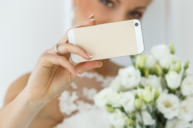 Beautiful bride with bouquet and smartphone